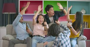 Young friends watching football game on TV together at home and celebrating a goal stock video