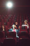Young friends watching movie in cinema theater Stock Photography