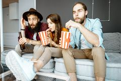 Friends watching TV at home stock image