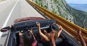 Young friends waving their arms while driving fast in convertible