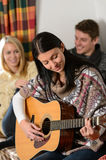 Young friends in winter cottage play guitar Stock Images