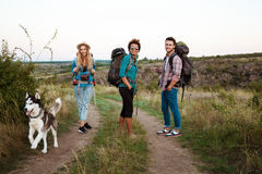 Young Friends With Backpacks And Huskies Smiling, Traveling In Canyon. Royalty Free Stock Photography