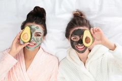 Free Young Friends With Facial Masks  Fun On Bed At Pamper Party, Top View Stock Images - 155999364