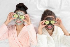 Free Young Friends With Facial Masks Having Funon Bed At Pamper Party, Top View Royalty Free Stock Photo - 155999355