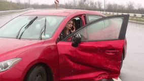Scared girl talking on the phone after a car accident in the rain, car is broken. Young frightened girl got into a car accident on the road in the heavy rain stock footage