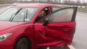 Girl got into car accident on the road in the heavy rain, she talks on the phone. Young frightened girl got into a car accident on the road in the heavy rain stock video footage