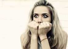 Portrait of an emotional girl. Young frightened girl with hands pressed to her face against a light background Stock Images