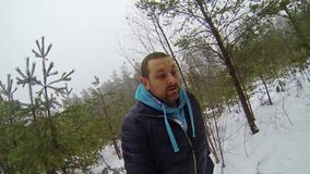 Young, frightened man running through the winter forest. stock video footage