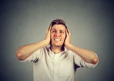 Stressful man suffering from noise. Young frowning man covering ears with hands looking frustrated with noise from loud neighbors stock image