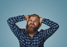 Young frowning man covering ears with hands looking up royalty free stock photos