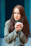 Young frozen woman with coffee Royalty Free Stock Image