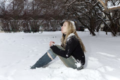 The young frozen woman under the falling snow Stock Photos