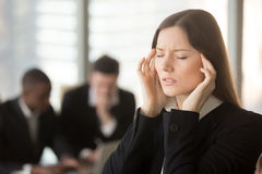 Young frustrated businesswoman feeling unwell dizzy during meeti. Young frustrated businesswoman feels unwell dizzy during meeting, touching massaging temples Stock Image