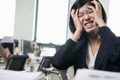 Young frustrated businesswoman sitting at desk with head in hands Stock Photo