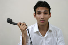 Young frustrated man with phone. Angry young frustrated man with the phone receiver Stock Image