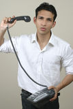 Young frustrated man throwing phone in anger. Upset young businessman throwing phone in desperation Stock Photography