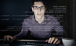 Young Frustrated Programmer. Young man with glasses sitting in front of his computer, programming. the code he is working on php can be seen through the screen stock photos