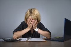 Young frustrated and stressed business woman crying sad at office desk working with laptop computer overwhelmed by paperwork workl royalty free stock photo