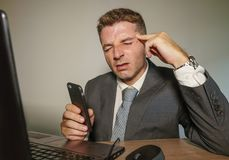 Young frustrated and stressed businessman in suit and tie working overwhelmed at office laptop computer desk suffering headache. And migraine feeling sick in stock photography