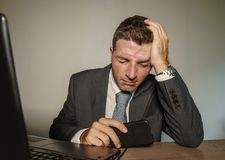 Young frustrated and stressed businessman in suit and tie working overwhelmed at office laptop computer desk suffering headache. And migraine feeling sick in royalty free stock images