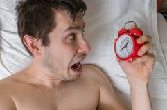 Young frustrated and stressed man is late. He is waking up, looking at alarm clock. Stock Images