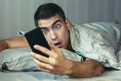 Young frustrated and stressed man is late. He is waking up, looking at smartphone and is shocked. The concept of a modern rhythm o royalty free stock images