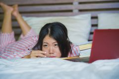 Young frustrated and tired Asian Japanese university student woman feeling bored and lazy preparing exam studying with laptop stock image
