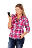 Young frustrated woman looking at a mobile phone.  Royalty Free Stock Photos