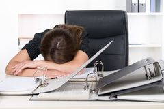 Young frustrated woman is lying in front of a pile of files Stock Image