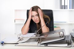 Young frustrated woman is sitting in front of a pile of files. A young frustrated businesswoman is sitting in front of a pile of files at the desk in the office Stock Photo