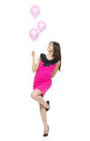 Young full body woman with pink balloons. As a present for birthday party smiling and looking at the corner on a white background Stock Photo
