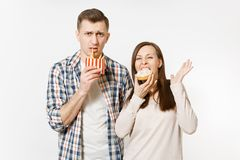 Young fun couple, man, woman in casual clothes eating, holding colorful donuts, french fries isolated on white stock images