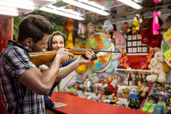 Young fun couple playing shooting games. At amusement park royalty free stock photo