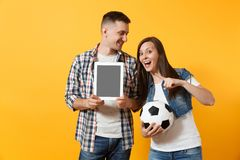 Young fun couple supporter, woman man, football fans cheer up support team, holding tablet pc computer with blank black. Young fun couple supporter, women man royalty free stock photos