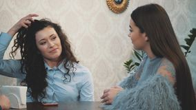Young fun girl girlfriends met in a cafe. During this, they talk about the problems and show a jolly look. Have long hair stock video footage