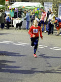 Young fun runner. A young girl finishing a fun run with great determination Royalty Free Stock Photography