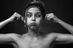 Woman inflates cheeks. Young fun woman on black background inflates her cheeks, shows ears, grimacing, monochrome Stock Photos