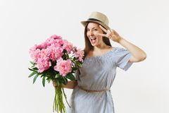 Young fun woman in blue dress, hat holding bouquet of pink peonies flowers, showing victory sign at eye isolated on. White background. St. Valentine`s Day royalty free stock images
