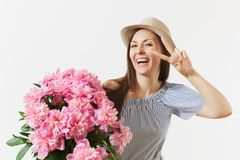 Young fun woman in blue dress, hat holding bouquet of pink peonies flowers, showing victory sign at eye isolated on. White background. St. Valentine`s Day royalty free stock photo