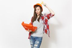 Young fun woman in protective hardhat holding opened case with instruments or toolbox and beating herself on head with. Toy hammer isolated on white background stock photography
