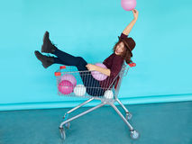 Young funky woman sitting in shopping cart over blue wall Stock Photography
