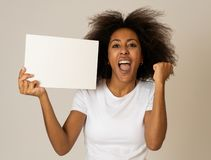 Young funny african american woman holding blank board for advertisement looking excited. Funny and beautiful african american woman showing and pointing at royalty free stock images