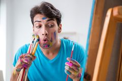 The young funny artist working on new painting in his studio. Young funny artist working on new painting in his studio Stock Photo