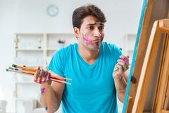 The young funny artist working on new painting in his studio. Young funny artist working on new painting in his studio Stock Photos