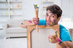 The young funny artist working on new painting in his studio. Young funny artist working on new painting in his studio Royalty Free Stock Images