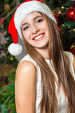Young funny beautiful fashion model with dark eyes, brown hair and santa hat celebrating new year at home. new year decoration, wi Royalty Free Stock Photos