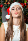 Young funny beautiful fashion model with dark eyes, brown hair and santa hat celebrating new year at home. new year decoration, wi Stock Photos