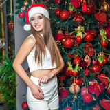 Young funny beautiful fashion model with dark eyes, brown hair and santa hat celebrating new year at home. new year decoration, wi Royalty Free Stock Image
