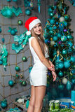 Young funny beautiful fashion model with dark eyes, brown hair and santa hat celebrating new year at home. new year decoration, wi Stock Photo