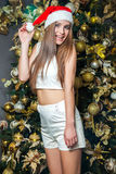 Young funny beautiful fashion model with dark eyes, brown hair and santa hat celebrating new year at home. new year decoration, wi. Th positive emotion posing Stock Photography